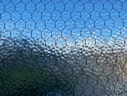 Close view stippled, opaque safety glass with wire mesh running through it. Indistinct blue sky and city barely visible through it, creating abstract background texture.