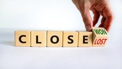 Close won or lost symbol. Businessman turns the wooden cube and changes words Close won to close lost. Beautiful white background, copy space. Business and close won or lost concept.