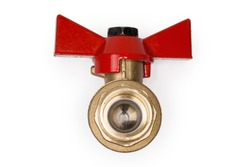 Closed ball valve with brass body and red butterfly handle on a white background, view of the valve insides from threaded connection side close-up in selective focus