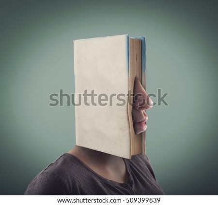 Closed book covering a face and the nose and mouth are coming out of it.