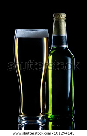 Closed bottle of beer  and full glass on dark background