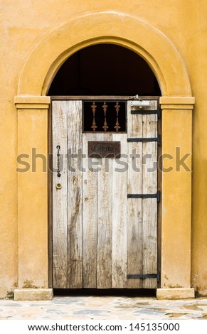 Closed door wooden covered with wrought iron of old building