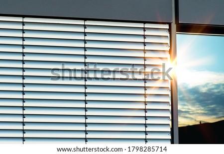 Closed external metal aluminium jalousie with reflections of sunrays  Foto d'archivio ©
