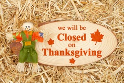 Closed for Thanksgiving message with a lady scarecrow with straw hay with wood sign