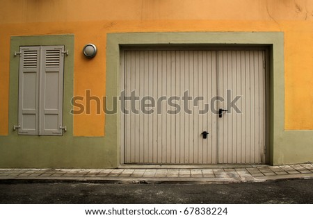 Closed garage door and window with closed shutters in a pink facade in a street
