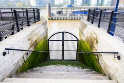 Closed gate on a riverside with stairs going down and a lot of green mold all over the steps and wall