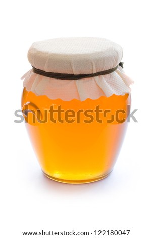 Closed glass jar full of honey isolated on white background