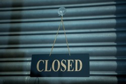 Closed golden sign on black background banner placed on the metal shutter. Concept of closed business, lockdown due to Covid-19 2020, crisis.