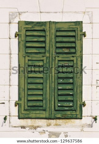 Closed green old wooden window in a stone house
