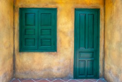 Closed green wooden door and window on old yellow wall, Hoi An, Vietnam, close up
