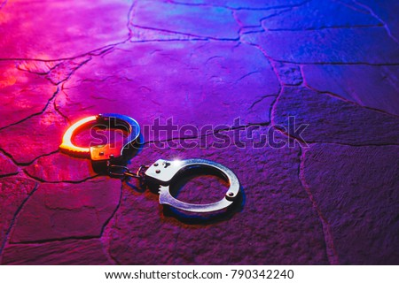 Closed handcuffs on the street pavement at night with police car lights / high contrast image - Shutterstock ID 790342240