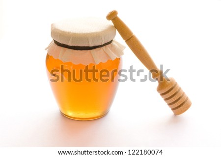 Closed jar full of honey and stick isolated on white background