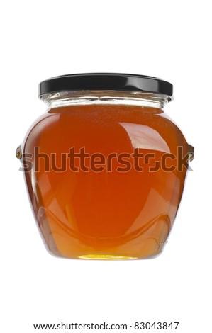 Closed jar of golden honey over white