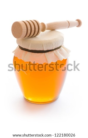 Closed jar of honey and stick isolated on white background