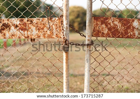 Closed lock with a chain on an old metal fence