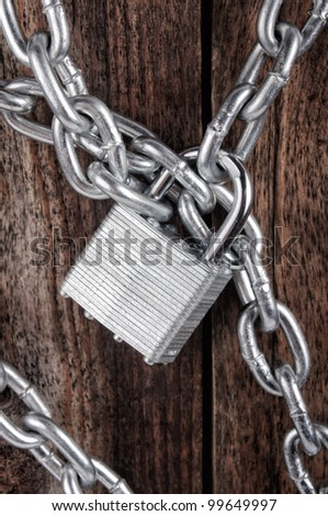 closed lock with a chain on an old wooden background