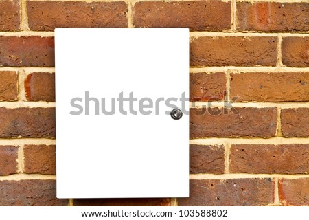 Closed locked white cupboard on a brick wall
