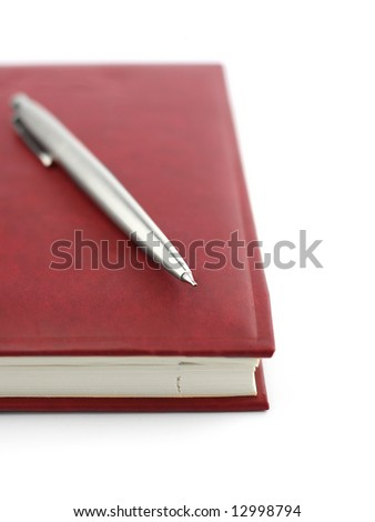 closed notebook with pen