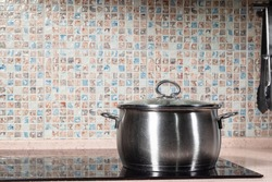 closed old steel stockpot on black ceramic stove in table at home kitchen