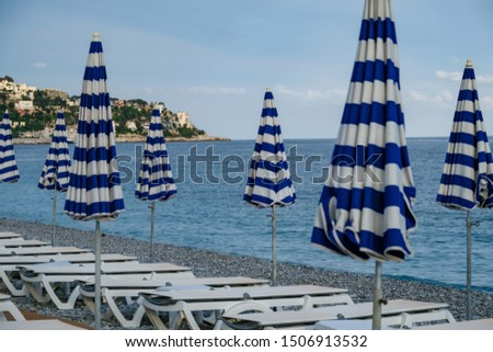 Closed parasols / sunshades, at the beach of Nice in France, Mediteranean sea coast. Peaceful waves, relaxing scenery. #1506913532