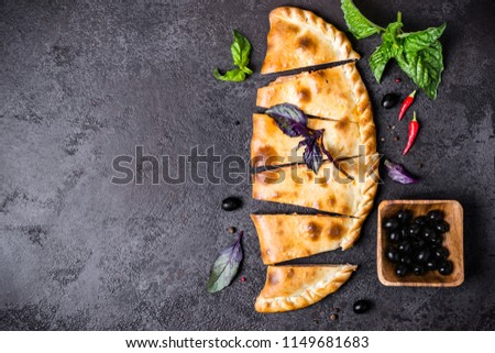 Closed pizza calzone is cut into pieces on a black table