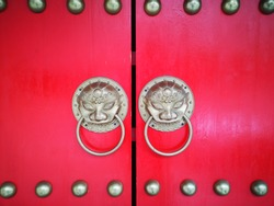 closed red door with Chinese brass knockers and rivets