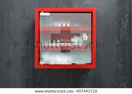 Closed red metal medical care box full of drugs hanging on a dark gray marble wall background. Front view #407443726