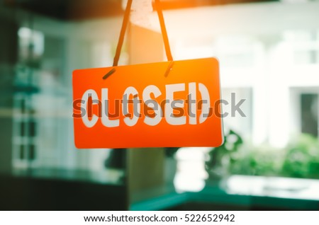 Closed sign hang on mirror door front of office room. Business and service concept. Vintage tone filter color style. #522652942