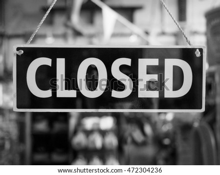 Closed sign in a shop showroom with reflections in black and white #472304236