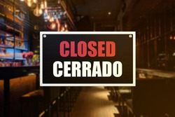 Closed sign of a bar or pub. With English and Spanish translation. Concept of Closure, suspension, or bankruptcy of a bar, restobar or pub.