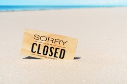 Closed sign on tropical sand beach with blue sky background. Summer vacation and travel holiday concept. Vintage tone fitler effect color style.