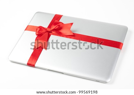 closed silver laptop gift with red ribbon isolated on white background