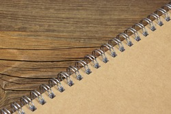 Closed Spiral Bound Notebook With Brown Paper Cover On Wood Rough Rustic Table Background Texture, Top View