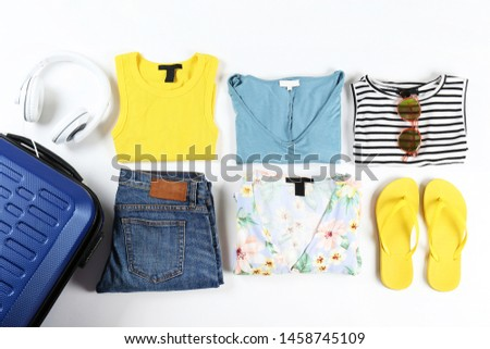 Closed suitcase fully packed with folded women clothing and accessories on the floor. Woman packing for tropical vacation concept. Female luggage w/ things. Background, close up, copy space, top view