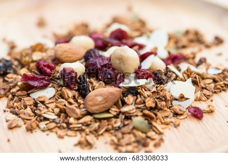 Closed up and blur breakfast healthy food, granola, musli, Organic oat, super food with honey, dried fruits and nuts on wooden plate