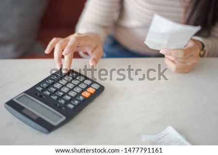 Closed up and focus on hand of young woman using a calculator and other hand take a bill which sitting on sofa and work on the table at cafe or co working space. co working space concept.