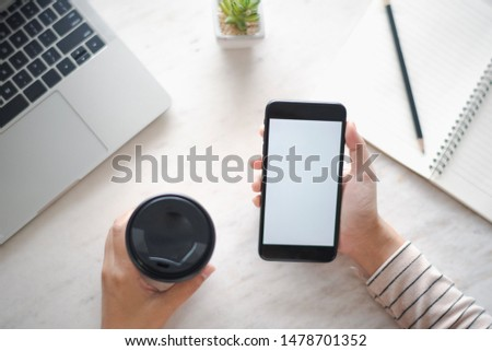 Closed up and focus on hand of young woman using a smartphone which show white display other hand hold a cup of coffee and have notebook put on table in near. see top view. co working space concept.