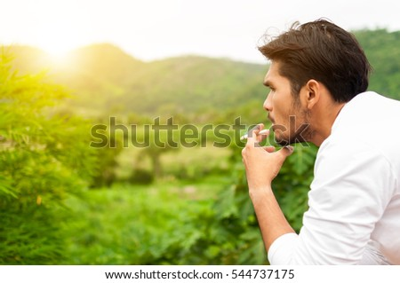 Closed up ,Bearded Asian Handsome man smoke cigarette making seriously decision something,outdoor office,Health and lifestyle concept,vintage tone
