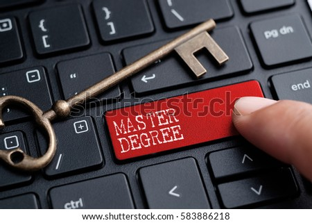 Closed up finger on keyboard with word MASTER DEGREE #583886218