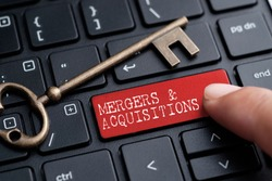 Closed up finger on keyboard with word MERGERS & ACQUISITIONS