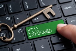 Closed up finger on keyboard with word STAY INFORMED