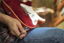 Closed up hand holding jack plug-in to the electric guitar, shallow DOF, selected focus