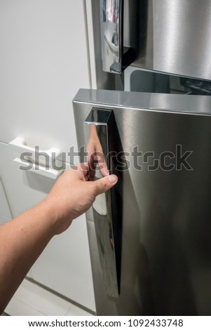Closed up hand opening the silver color handle of monochromatic refrigerator door. #1092433748