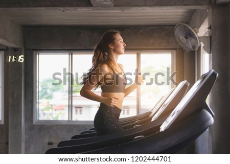 Closed up happy young woman exercise treadmill running in modern gym, healthy life style concept. #1202444701