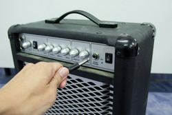 Closed up man hand holding jack audio plug-in to the guitar amplifier, selected focus
