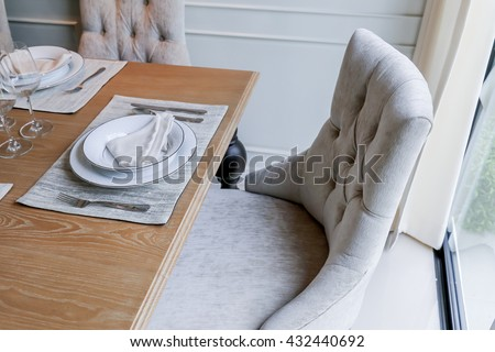 closed up nice dining chair with wooden table and dish sets interior design