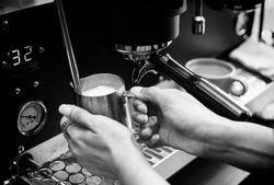 Closed up of barista's hand holding pitcher full of milk frothing from coffee machine. For making cappuccino or latte. Black and white tone