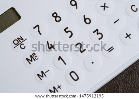 Closed up of white calculator buttons such as numbers, plus, minus, multiply and divind on black leather using as budget, loan, maths, investment banking and accounting. #1475912195