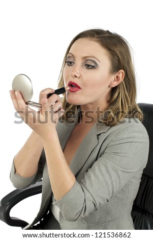 Closed up portrait of an attractive businesswoman applying lipstick while looking at her pocket mirror