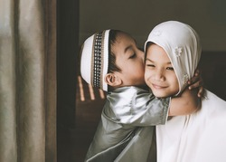 Closed-up shot of Asian Muslim kids. a young sister and brother sibling in Muslim traditional dress.Happy and looking to the camera.Concept of a happy kid in Ramadan or family bonding.